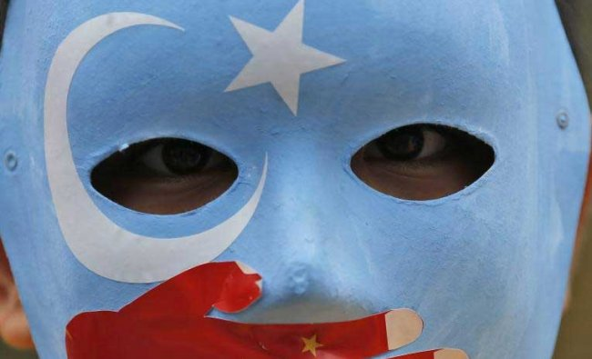 A child from the Uighur community living in Turkey wears a mask in the colours of the flag what ethnic Uighurs call \'East Turkestan\', with a painted hand with the colours of China\'s flag, during a protest in Istanbul, Tuesday, Nov. 6, 2018, against what they allege is oppression by the Chinese government to Muslim Uighurs in the far-western Xinjiang province. AP/PTI