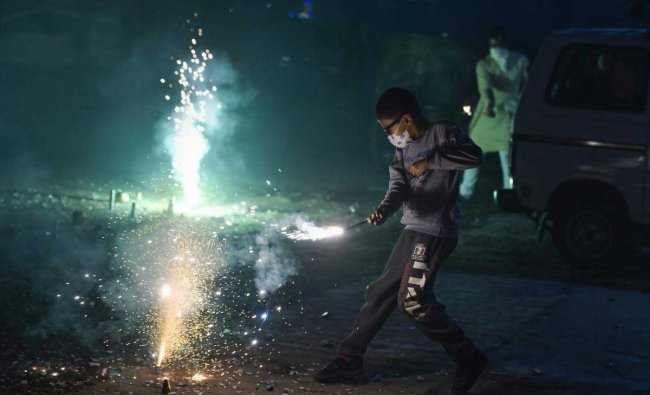A boy wearing pollution mask burns crackers during Diwali celebrations, in New Delhi, Wednesday, Nov. 07, 2018. According to the officials, Delhi recorded its worst air quality of the year the morning after Diwali as the pollution level entered \'severe-plus emergency\' category due to the rampant bursting of toxic firecrackers. (PTI Photo)