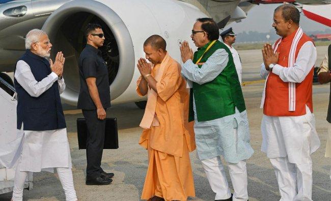 Prime Minister Narendra Modi being received by Uttar Pradesh Chief Minister Yogi Adityanath, UP BJP chief Mahendra Nath Pandey and UP Deputy Chief Minister Keshav Prasad Maurya on his arrival, in Varanasi, Monday, Nov 12, 2018. (PIB Photo via PTI)