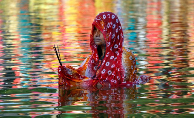 A Hindu woman worships the Sun god in the waters of a lake during the religious festival of Chhath Puja in Agartala, November 13, 2018. REUTERS