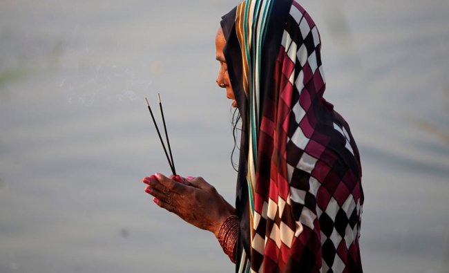 A Hindu woman worships the Sun god in the waters of the Sabarmati river during the religious festival of Chhath Puja in Ahmedabad, India, November 13, 2018. REUTERS