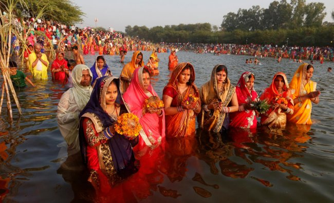 Hindu women hold offerings as they worship the Sun god in the waters of a lake during the Hindu religious festival of Chhath Puja in Chandigarh, November 13, 2018. REUTERS