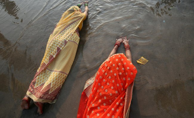 Hindu women lie as they worship the Sun god in the waters of the Arabian Sea during the religious festival of Chhath Puja in Mumbai, November 13, 2018. REUTERS