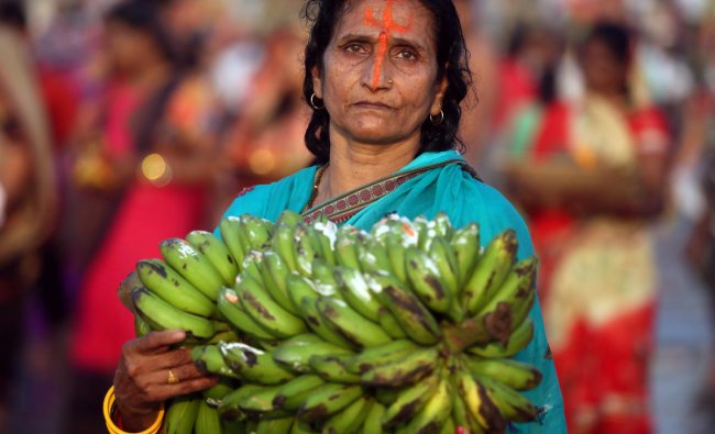 A Hindu woman holds bananas as she worships the Sun god in the waters of the Arabian Sea during the religious festival of Chhath Puja in Mumbai, November 13, 2018. REUTERS