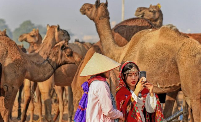 Tourists dressed in traditional attire take a selfie at the annual Pushkar Camel Fair 2018, in Pushkar. PTI photo