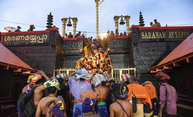 Devotees enter the Sabarimala temple as it opens amid tight security, in Sabarimala. PTI Photo