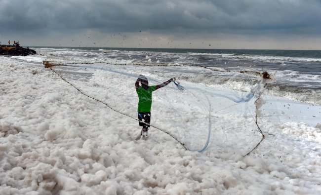 A fisherman casts his fishing net over the frothed water at the Marina beach, in Chennai. PTI photo