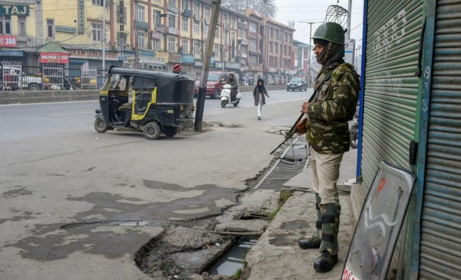 A CRPF jawan stands guard during a strike call given by the separatist leaders against the killing of a Tehreek-e-Hurriyat leader, at Lal Chowk in Srinagar. PTI photo