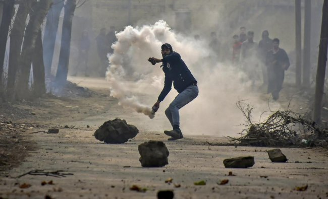 Chattergam: A protester hurls stones on security personnel near the encounter site at Kuthipora village, Chattergam in Budgam district of central Kashmir, Wednesday, Nov. 28, 2018. Two militants including most wanted Lashkar-e-Taiba militant Naveed Jhutt, who was allegedly involved in the assassination of journalist Shujaat Bukhari, were killed in the encounter. (PTI Photo/S Irfan)