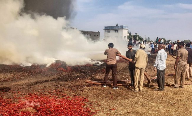 Rajkot: Fire personnel try to control fire at a red chilli heap after a fire broke out in Agriculture Product Marketing Committee (APMC) yard at Gondal town in Rajkot district of Gujarat, Wednesday. (PTI Photo)