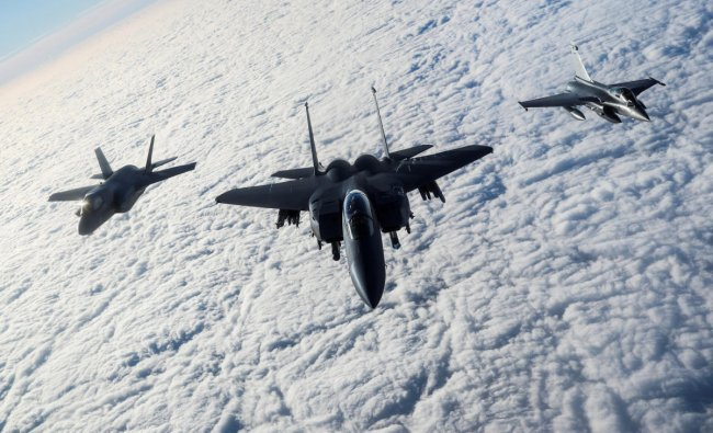 An RAF F-35B Lightning, a USAF F-15E Strike Eagle and a French Rafale fly over The English Channel in formation during the \