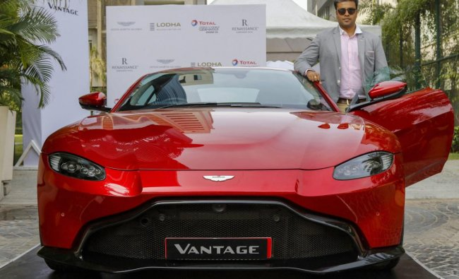 Aston Martin India Business Head Sandeep Gupta poses for photos with newly-launched Aston Martin V8 Vantage car, in Ahmedabad. (PTI Photo)