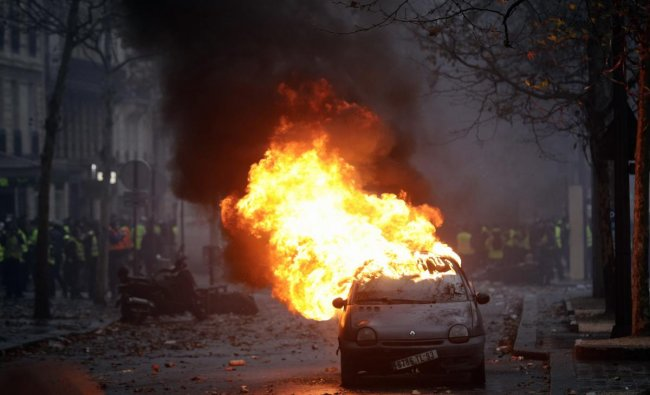 A car burns near the Champs-Elysees avenue during a demonstration in Paris. French authorities have deployed thousands of police on Paris\' Champs-Elysees avenue to try to contain protests by people angry over rising taxes and Emmanuel Macron\'s presidency. (AP/PTI Photo)