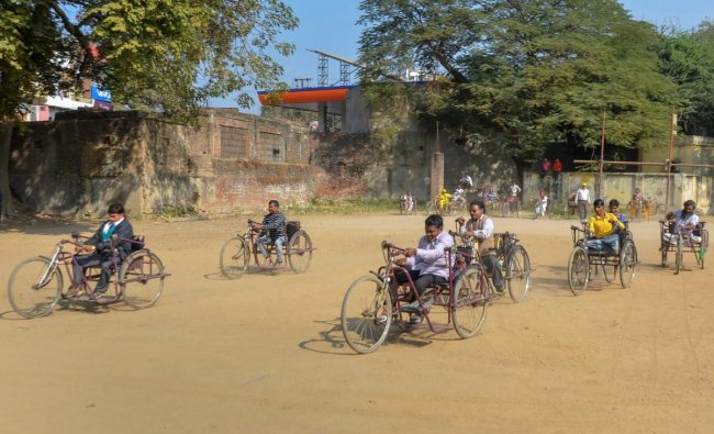 Differently abled people take part in the tricycle race to mark the \'International Day of Persons with Disabilities\', in Mirzapur. (PTI Photo)