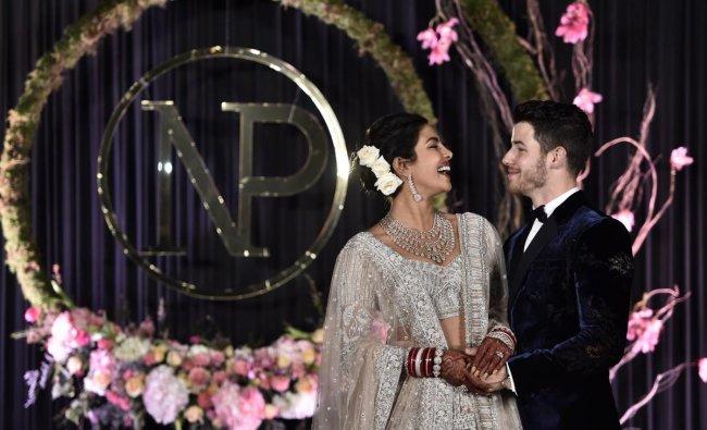 Priyanka Chopra and Nick Jonas pose for photos during their wedding reception, in New Delhi. (PTI Photo)
