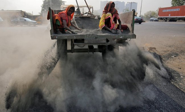 Labourers spread ash over newly constructed road tarmac to dry it and fill in the gaps, on the outskirts of Ahmedabad. (Reuters Photo)