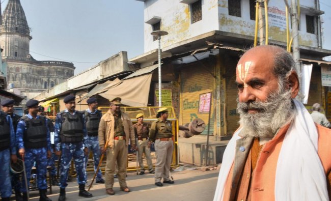 A sadhu walks along a road as police and RAF personnel keep vigil, on the anniversary of Babri mosque demolition, in Ayodhya. (PTI Photo)