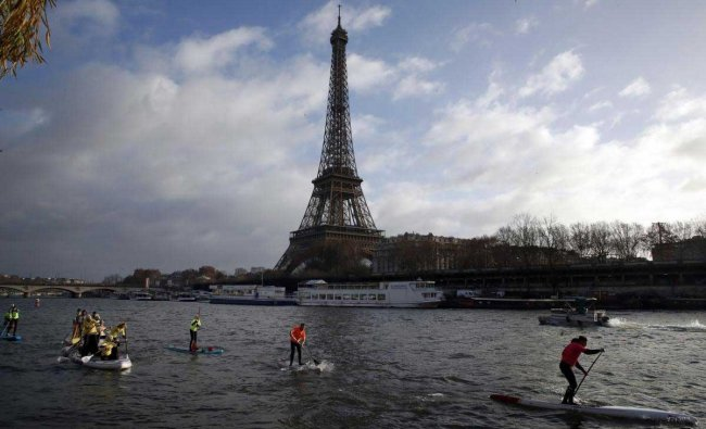 Competitors paddle on the Seine river during the Nautic Paddle race as part of the Nautical Paris Boat show, an exhibition dedicated to all the watersports, in Paris, Sunday, Dec. 9, 2018. The Eiffel Tower is seen background. AP/PTI