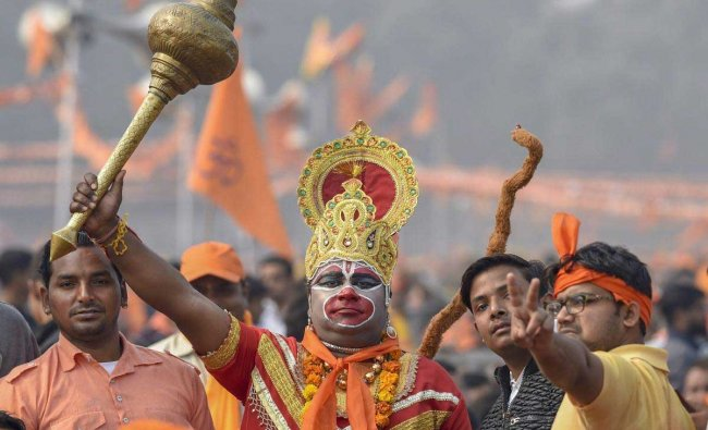 A supporter of Vishwa Hindu Parishad's (VHP) dressed as Lord Hanuman lifts a mace during 'Dharma Sabha' event, in which thousands of people gathered at Ramlila Maidan to press for the construction of Ram Temple in Ayodhya, days before Parliament\'s winter session commences, in New Delhi, Sunday, Dec. 9, 2018. (PTI Photo)