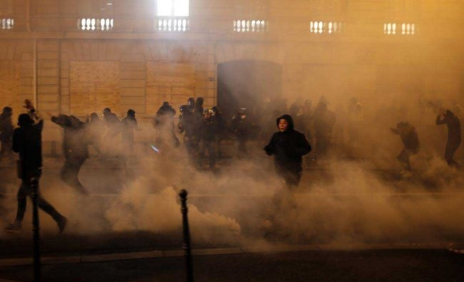 Demonstrators run away to avoid tear gas during clashes Saturday, Dec. 8, 2018 in Paris. Crowds of yellow-vested protesters angry at President Emmanuel Macron and France\'s high taxes tried to converge on the presidential palace Saturday, some scuffling with police firing tear gas, amid exceptional security measures aimed at preventing a repeat of last week\'s rioting. AP/PTI