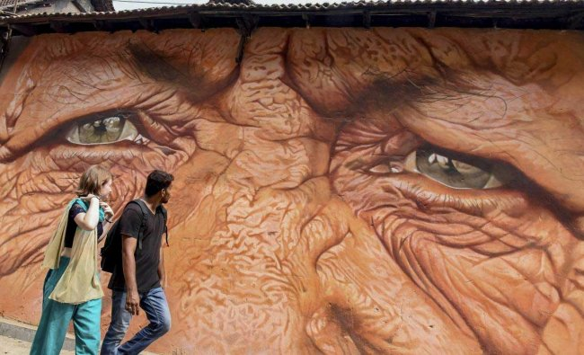 A couple walks past a painting on a wall which will be part of the 4th edition of \'Kochi Muziris Biennale\', an international exhibition of contemporary art to be held on Dec.12th, in Kochi, Monday, Dec. 10, 2018. (PTI Photo)