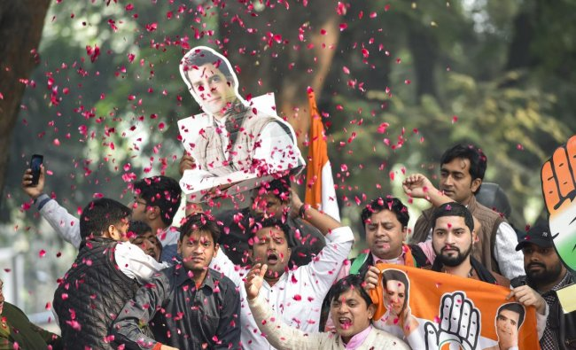 Congress Party workers display Congress President Rahul Gandhi\'s cutout as they celebrate after initial trends showed the party leading in the state Assembly election results, at the Congress headquarters in New Delhi, Tuesday, Dec.11, 2018. (PTI Photo)