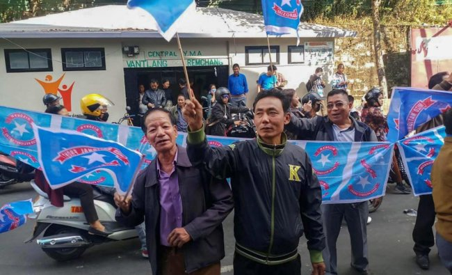 Mizo National Front (MNF) workers hold their party flag as they celebrate the party\'s victory in the states Assembly elections, at Party head office, in Aizawl, Tuesday, Dec. 11, 2018. (PTI Photo)