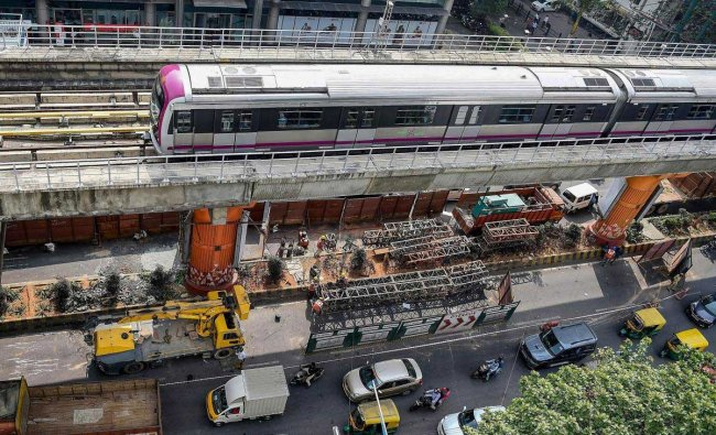 A metro train runs on the elevated corridor, as work to fix the damaged pillar underneath is in progress, in Bengaluru, Wednesday, Dec. 12, 2018. (PTI Photo)