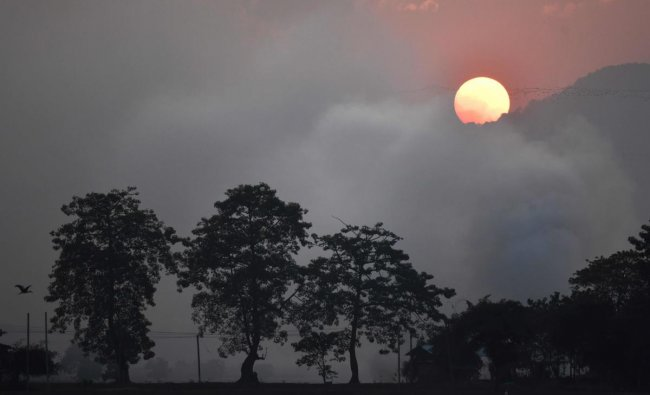Birds fly as the sun sets behind a mountain range at Mayong village, some 40kms from Guwahati on December 16, 2018. (AFP)