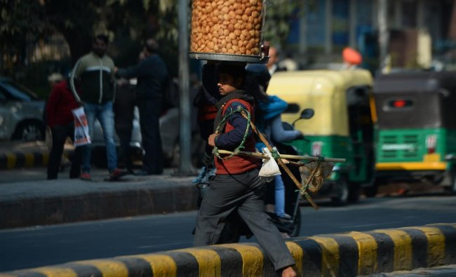 An Indian vendor carrying a container of golgappa snacks on his head crosses a road in New Delhi on December 20, 2018. (Photo by Sajjad HUSSAIN / AFP)