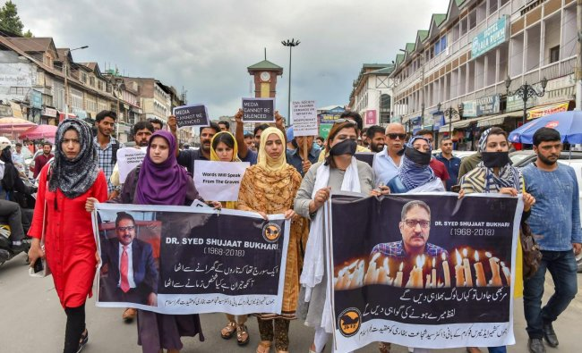 Journalists hold placards during a silent protest march against the killing of Rising Kashmir newspaper editor-in-chief Shujaat Bukhari, in Srinagar on June 26.