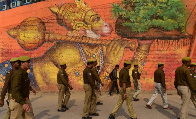 Policemen walk past a wall painted with a picture of Lord Hanuman during \'Nagar Pravesh\' procession of Panch Dashnam Atal Akhara sadhus for the Kumbh Mela 2019, in Allahabad on December 13.