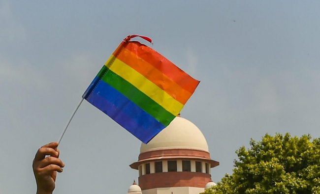An activist waves a rainbow flag after the Supreme Court verdict decriminalised consensual gay sex, outside the Supreme Court in New Delhi on September 6. A five-judge constitution bench of the Supreme Court unanimously decriminalised part of the 158-year-old colonial law under Section 377 of the IPC which criminalises consensual unnatural sex, saying it violated the rights to equality.