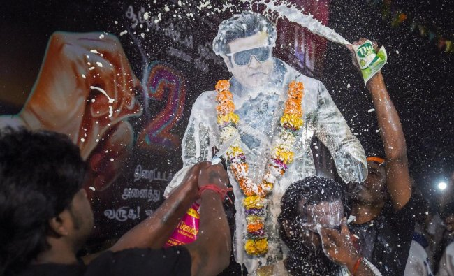 Fans pour milk on a cutout of Tamil actor Rajinikanth to celebrate the release of his film \'2.0\', in Mumbai on November 29.
