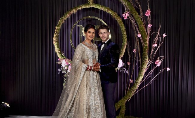 Newly-wed Bollywood actor Priyanka Chopra and American singer Nick Jonas pose for photos during their wedding reception, in New Delhi, on December 4.