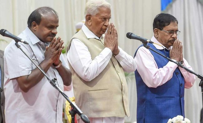 Karnataka Governor Vajubhai Vala flanked by Chief Minister HD Kumaraswamy (L) and Deputy CM G Parameswara during the swearing-in ceremony for the cabinet expansion of coalition government of Congress-JD(S), in Bengaluru. PTI Photo