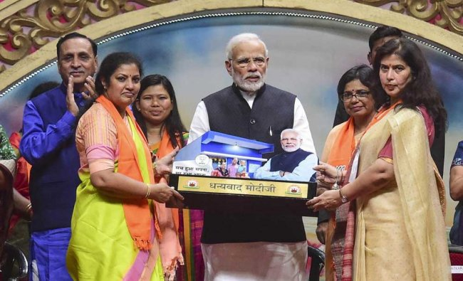 Prime Minister Narendra Modi being felicitated by BJP women\'s wing leaders during their National Convention, in Ahmedabad. PTI Photo