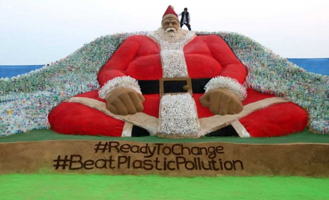 Sand artist Sudarsan Patnaik gives final touches to a sculpture representing Santa Clause surraunded by plastic bottles, depicting the message \'Beat Plastic Pollution\' on the eve of Christmas at Puri beach, some 65 kms from Bhubaneswar. AFP Photo
