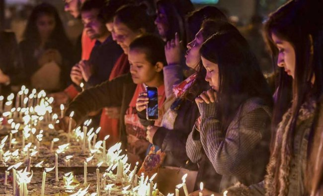 People light candles at the Sacred Heart Cathedral on the eve of Christmas Day in New Delhi. PTI Photo