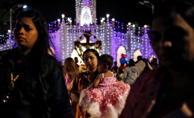 Worshippers arrive to attend a mass on Christmas Eve at a church in Mumbai. REUTERS Photo