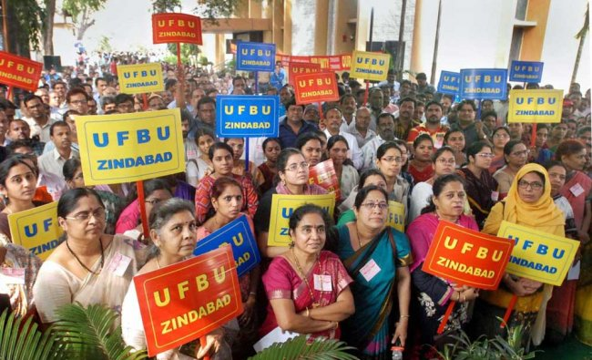 United Forum of Bank Unions (UFBU) members display placards during a protest against the proposed merger of Vijaya Bank and Dena Bank with Bank of Baroda, as part of their nation-wide strike, in Hyderabad. PTI Photo