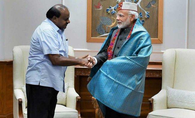 Prime Minister Narendra Modi shakes hands with Karnataka Chief Minister HD Kumaraswamy during a meeting, in New Delhi. PTI Photo