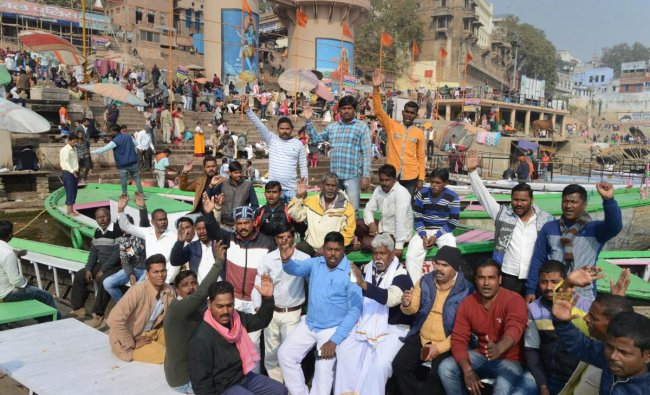 Boatmen raise slogans during a protest against the newly-inaugurated cruise services which they claimed hampers their livelihood, at Rajendra Prasad Ghat, in Varanasi. PTI
