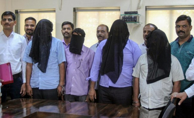Police personnel from Anti-Narcotics Cell of the Crime Branch with the four members caught in possession of 100 kgs of \'Fentanyl\', a drug banned in India, after a raid, in Mumbai. PTI