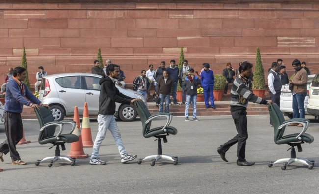 Workers move wheeled chairs at Parliament House, in New Delhi. PTI