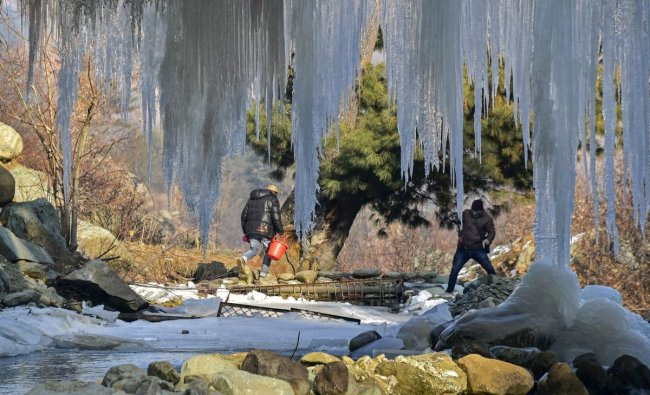 Men cross a stream as huge icicles hang from a bridge at Tangmarg in district Baramulla of north Kashmir, Sunday, December 30, 2018. The residents in Kashmir experienced huge relief from the intense cold wave conditions as the mercury improved by several degrees across the valley and Ladakh region last night, even as the minimum temperature continued to settle below the freezing point. PTI