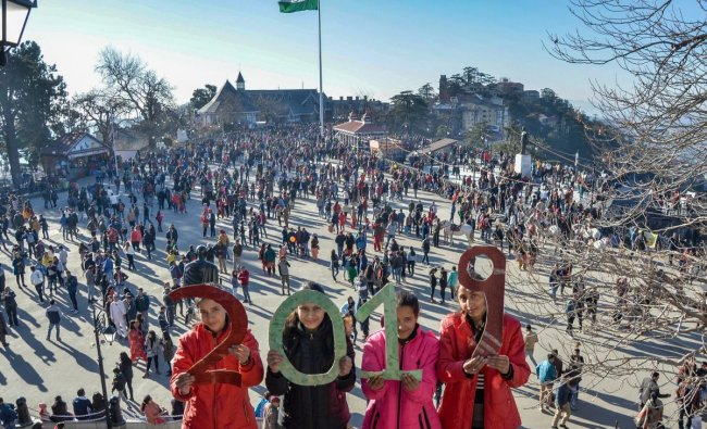Youngsters hold cutouts that read \'2019\', on the New Year\'s eve, at Ridge in Shimla. PTI