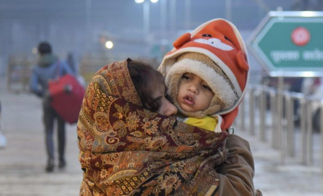 A child and mother wrapped in warm clothes wait at the station as trains run late on a cold, foggy winter morning, in Allahabad. PTI