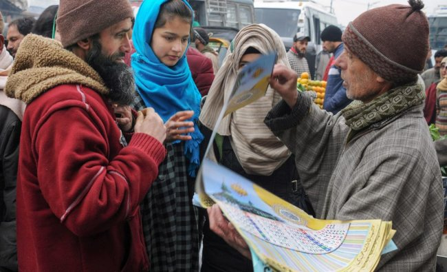 People buy calendars on the first day of the new year 2019, at a market in Srinagar. PTI