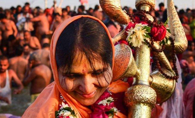 A Sadhvi of Juna Akhara takes a holy dip holding a trident at Sangam on the auspicious Makar Sankranti day during the Kumbh Mela, or pitcher festival in Allahabad. PTI photo